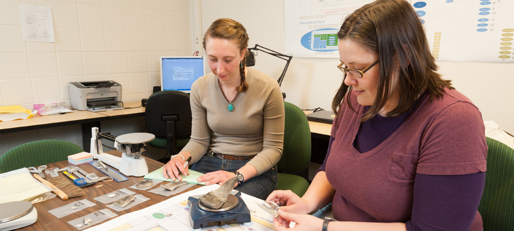 Colorado State University Archaeology graduate students Becca Simon and Kristi Gensmer measure specimens in the Historical Archaeological Laboratory.
