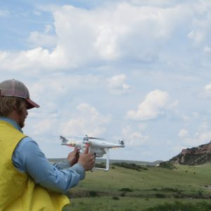 Graduate student Kelton Meyer at Lindenmeier Folsom archaeology site working with a drone in 2018