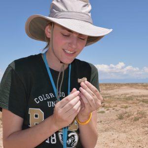 Carson Black with a Vulpavus left ramus during the 2017 Paleontology Field School.