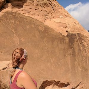 Woman observes a boulder with glyphs on it