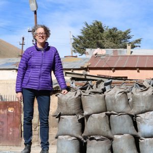 Mary Van Buren, standing next to bags of mineral ore in highland Bolivia